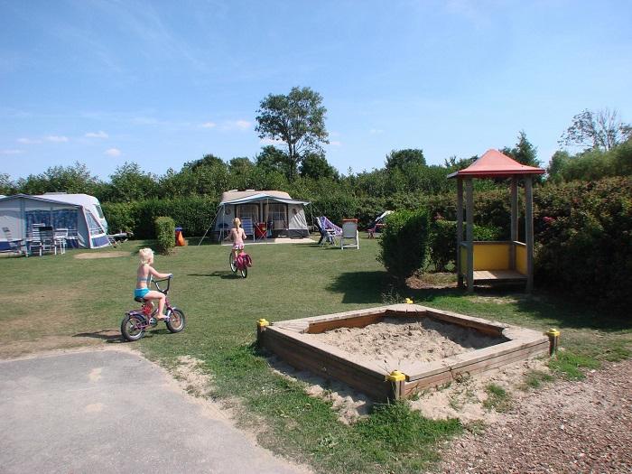 Zandbak en op de achtergrond kampeerplaatsen