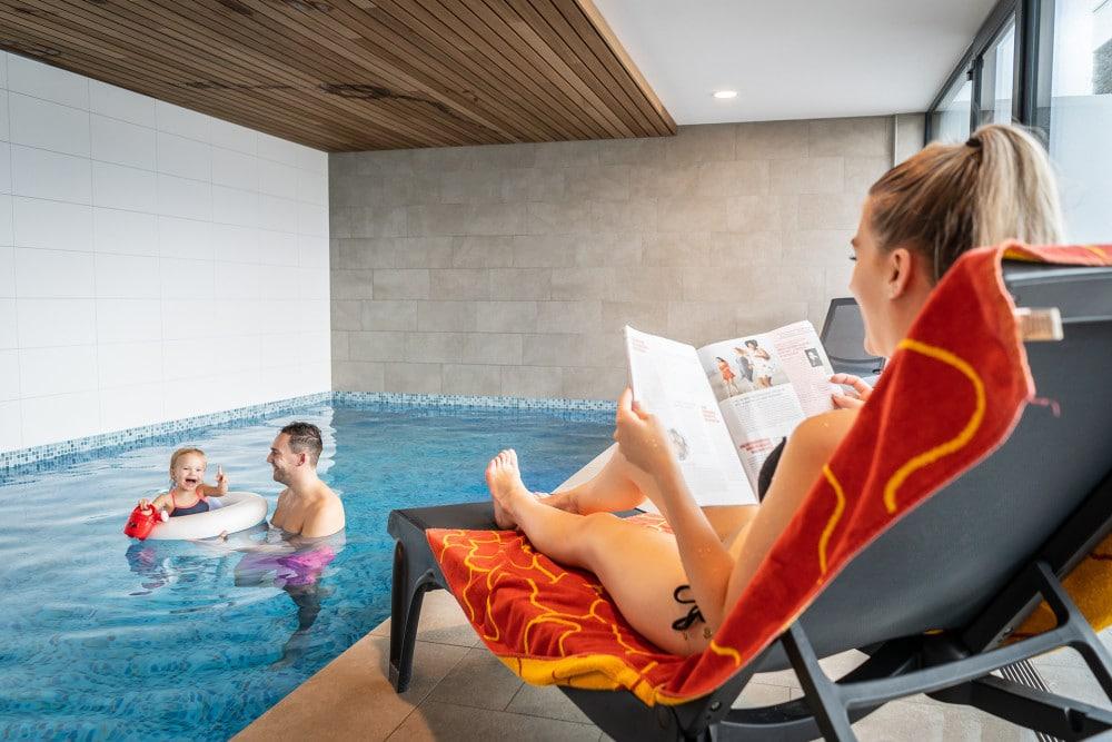 Ouders met kind bij zwembad, villapark Nederland
